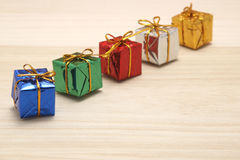 Some colorful gift boxes with gold ribbons. Some colorful gift boxes with gold ribbons on wood Stock Photo