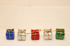 Some colorful gift boxes with gold ribbons. Some colorful gift boxes with gold ribbons on wood Stock Image