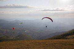 Some colorful paragliders flying over Monte Cucco Umbria, Italy, with some faint sunrays. Some colorful paragliders flying over Monte Cucco Umbria, Italy with royalty free stock images