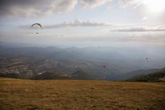 Some colorful paragliders flying over a mountain scenery, with some faint sunrays. Some colorful paragliders flying over a mountain scenery with some faint royalty free stock photos