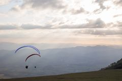Some colorful paragliders flying over a mountain scenery, with some faint sunrays in the background.  royalty free stock image