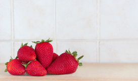 Some colorful strawberries inside a kitchen. A composition with some strawberries on a wooden chopping board, inside a kitchen, space for text, lanscape cut Stock Photos