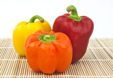 Some colourful peppers on table mat. Yellow, red, orange peppers on table setting Royalty Free Stock Photo