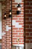 Columns of brick with lanterns. Some columns of brick with lanterns in a restaurant architecture. A glass of champagne on a table Stock Photo