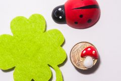 Some common luck symbols on a white surface. Some common luck symbols fourleaf clover, ladybird and a golden coin with a tiny toadstool on it on a white surface Royalty Free Stock Image