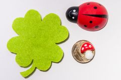 Some common luck symbols on a white surface. Some common luck symbols fourleaf clover, ladybird and a golden coin with a tiny toadstool on it on a white surface Stock Image