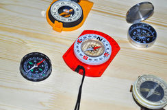 Some compasses are located on the Board. Magnetic compasses lies on textured wood surfaces Stock Photo