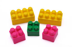Some construction set toys pieces. A photo taken on some yellow, green, pink construction set toys pieces against a white backdrop stock photography