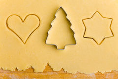 Some cookie cutter shapes on dough. Some christmas cookie cutter shapes on raw cookie dough stock images