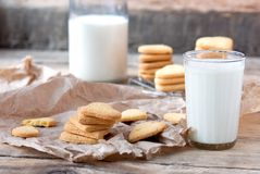 Some cookies and a glass of milk on the wooden table Stock Image
