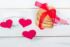 Some cookies hearts tied with red ribbon. And textile hearts around Royalty Free Stock Image