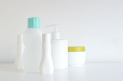 Some cosmetic, perfume and lotion bottles on a white table. Empty copy space for editor`s text stock images
