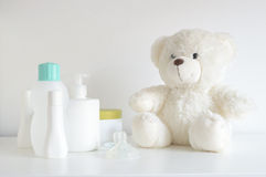Some cosmetic, perfume and lotion bottles on a white table next to a teddy bear and a pacifier. Empty copy space for editor`s text royalty free stock image