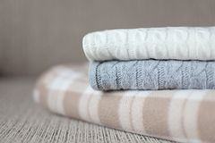 Some cozy plaids on a sofa. Autumn or winter concept. Woolen plaids or sweaters on a grey sofa, winter or autumn season Royalty Free Stock Photo