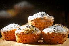 Some creamy muffins with caster sugar. On black background royalty free stock images