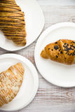 Some croissants on a white plate on the table. Three croissants on a white plate on the table Royalty Free Stock Photo