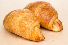 Some croissants on a wooden surface Stock Photos