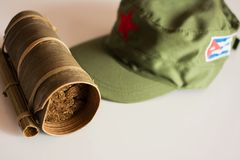 Cuban cigars rolled in banana leaf and military cap on the backg. Some Cuban cigars rolled in banana leaf and military cap on the background stock photos