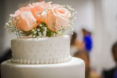 Roses in the cake. Some cups and bread on the table to celebarte the weeding party royalty free stock images