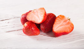 Some cut strawberry berries on white boards Stock Images