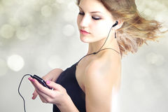 Some are dancing, runing others are flying. Attractive teen age girl listening to music with mp3 player and earphone with hair blowing in the wind isolated on Royalty Free Stock Images