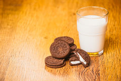 Some dark glass of milk and cookies on a blurred background. Some dark glass of milk and cookies on a blurred  background Stock Images