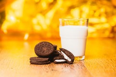 Some dark glass of milk and cookies on a blurred background. Some dark glass of milk and cookies on a blurred  background Royalty Free Stock Images