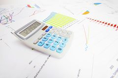 Some data charts with a calculator on the table. Calculator over business data charts Stock Image