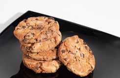 Some delicious chocolate cookies on a black plate  on white background Royalty Free Stock Photos
