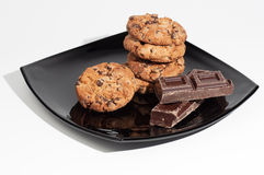 Some delicious chocolate cookies on a black plate  on white background. Some delicious chocolate cookies on a black plate with some chocolate pieces  on white Stock Photo