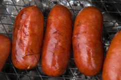 Some delicious grilled sausages with smell of smoke Stock Images