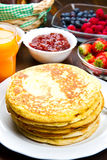 Some delicious pancakes on wooden table with fruits. Delicious pancakes on wooden table with fruits royalty free stock photography