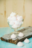 Some delicious pink macarons in a glass jar on a white wooden table with a robin egg blue background. Vintage Style. White and pink meringue on a blue wooden stock image