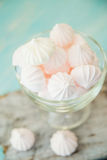 Some delicious pink macarons in a glass jar on a white wooden table with a robin egg blue background. Vintage Style. White and pink meringue on a blue wooden royalty free stock photo