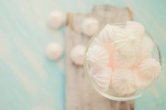 Some delicious pink macarons in a glass jar on a white wooden table with a robin egg blue background. Vintage Style. White and pink meringue on a blue wooden royalty free stock image