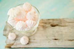 Some delicious pink macarons in a glass jar on a white wooden table with a robin egg blue background. Vintage Style. White and pink meringue on a blue wooden stock photography