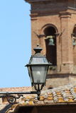 Some details of medieval Italian cities. Medieval street lamp with church tower in the background Royalty Free Stock Photos