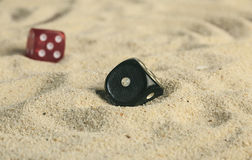 Some dices in the sand dunes.  Royalty Free Stock Photos