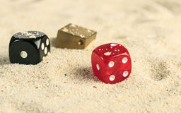 Some dices in the sand dunes.  Royalty Free Stock Photo