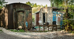 Some dilapidated shacks in the forest. Two ramshackle huts made from bricks and sheet metal. corrugated sheets of metal. gate with a fence. wheel trims stock images