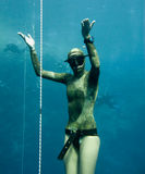 Some divers are watching the stopped freediver Stock Image