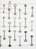 Some door keys aligned on old wooden surface, safety and security concept background.  stock images