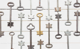 Some door keys aligned on old wooden surface, safety and security concept background Stock Photo