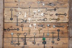 Some door keys aligned on old wooden surface, safety and security concept background.  royalty free stock photo