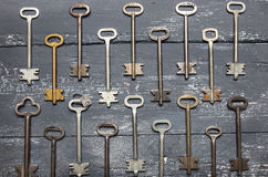 Some door keys aligned on old wooden surface, safety and security concept background.  royalty free stock image