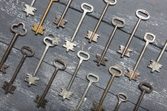 Some door keys aligned on old wooden surface, safety and security concept background Royalty Free Stock Photo