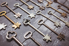 Some door keys aligned on old wooden surface, safety and security concept background Royalty Free Stock Photos