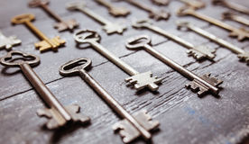 Some door keys aligned on old wooden surface, safety and security concept background.  stock photos