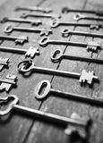 Some door keys aligned on old wooden surface, safety and security concept background Royalty Free Stock Photography