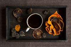 Black coffee and some dried orange slices on wooden tray. Flat l. Some dried orange peel, cones and dried orange slices with a cup of hot dlack coffee on black Royalty Free Stock Images